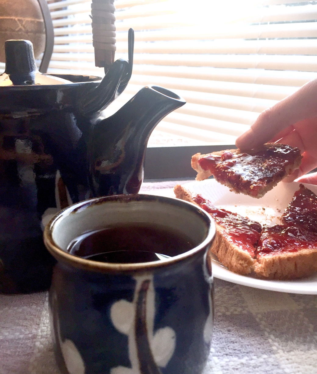 Teatime with toast, jam, and a blue teapot